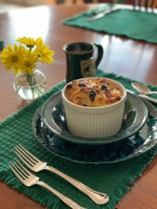 Bread Pudding in white ramakin on green plate with utentensil