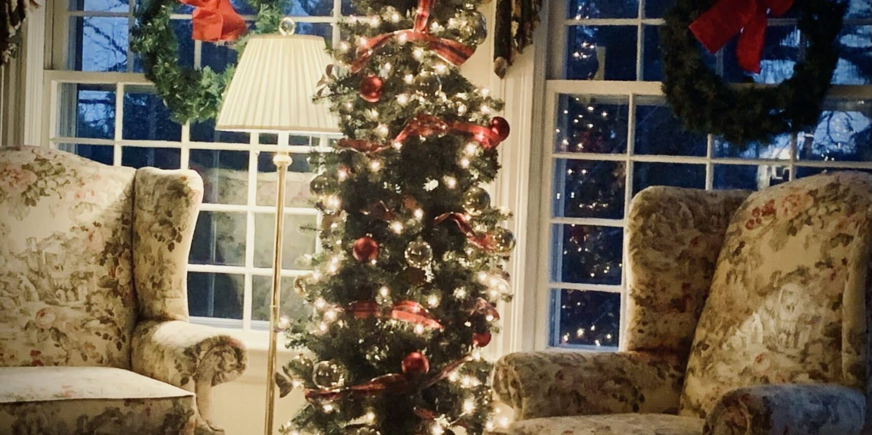decorated christmas tree flanked by wing chairs