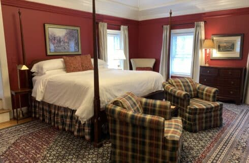 Deep red room with four post bed and club chairs in fron