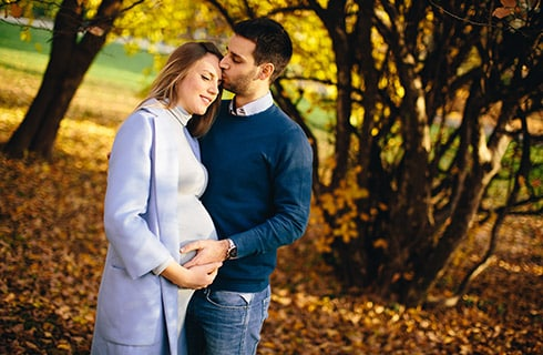 An Autumn landscape of orange leaves, green grasses, and trees in the background with a pregnant woman and her partner holding her belly while the man kisses her forehead.