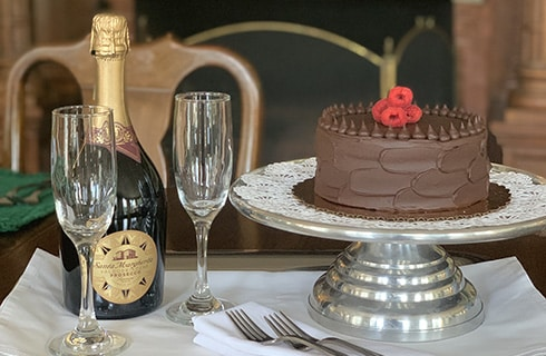 A white place setting with champaigne flutes, and champaigne bottle, next to a cake service and chocolate iced cake with raspberries on top.