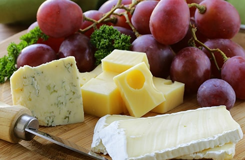 A wooden board with bleue cheese, mozzerella cheese, and grapes with a parsley garnish.