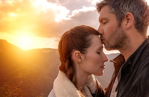 Sun setting behind a mountain between clouds in the background as a man kisses a woman on the forehead.