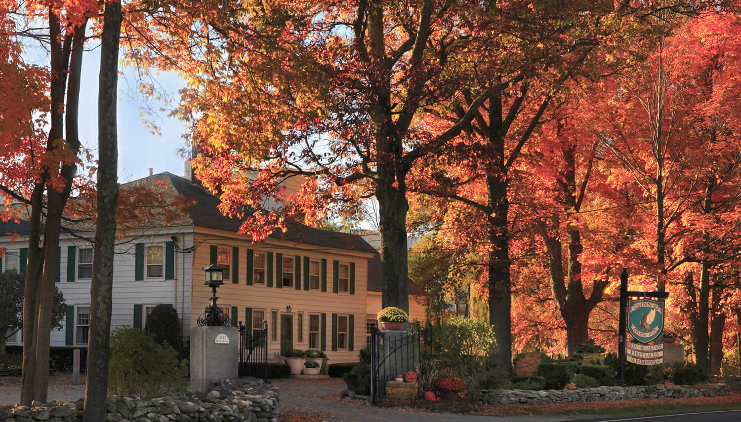Large white house with black roof and shutters set amid glowing fall foliage.