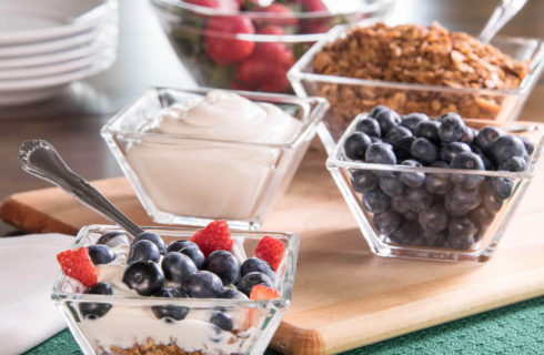 Bowls full of ingredients for yogurt parfait with strawberries, blueberries and granola.