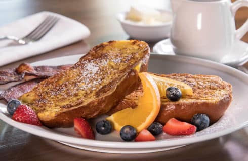 French toast garnished with orange slices and berries on a white plate with coffee in a white mug.