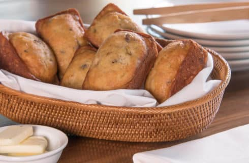 Cute little loaves of quick breads in a wicker basket with butter pats.