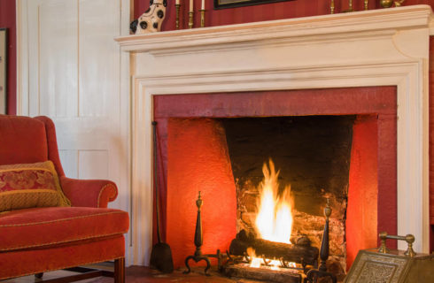 Plaster fireplace with a white mantle next to a red velvet chair in a room with red walls and white trim.