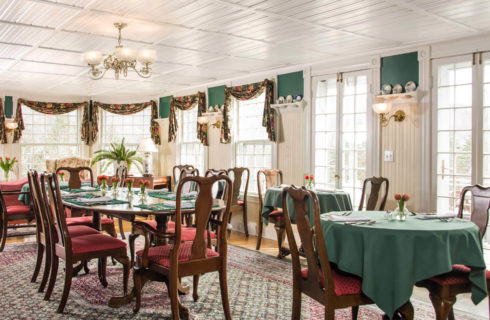 Bright dining rooom with large windows and various tables covered in green cloths set with napkins and silver.