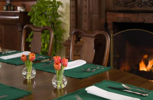 A wooden table set with green placemats and white napkins with silver and tulips in vases next to a fireplace.