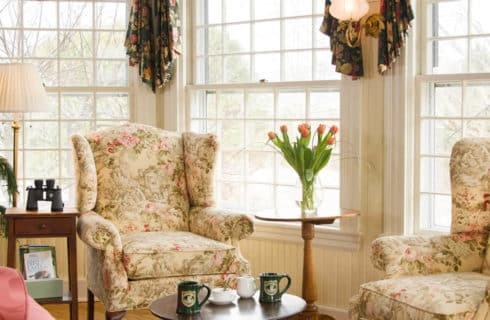 Charming sitting area with two cream and rose wingback chairs, a table with two mugs and large bright windows.