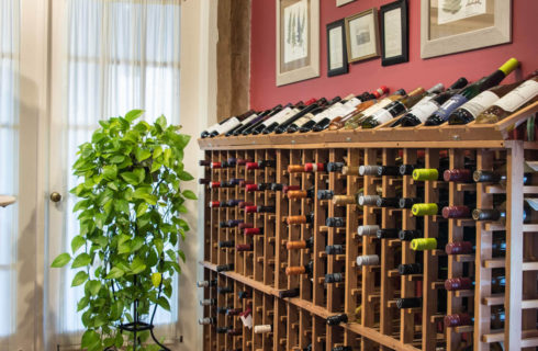 A wooden wine rack full of many bottles of wine next to a set of white french doors.