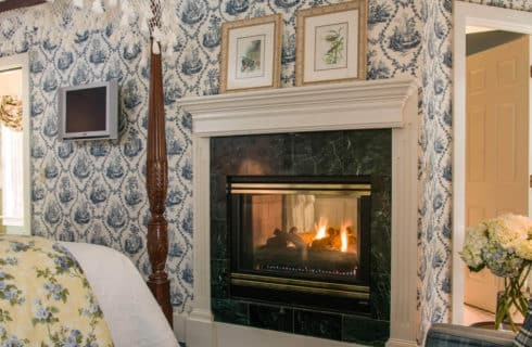 Fireplace with tiled face and white wood mantel in a bedroom with blue patterned wallpaper.