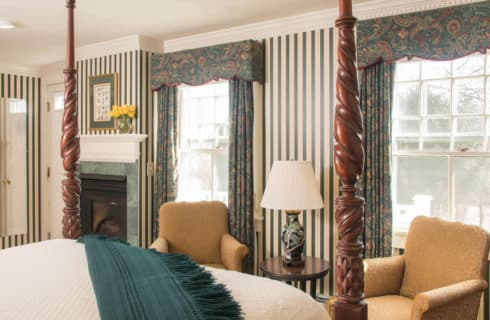 Charming room with a four-post bed, two chairs, green striped wallpaper, a fireplace faced in green marble and two large windows.