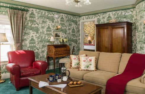 Bedroom decorated with green toile wallpaper, a wooden armoire and writing desk and a sofa and chair.