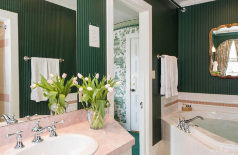 Green striped wallpaper in a bathroom with a pink vanity and a large soaking tub.
