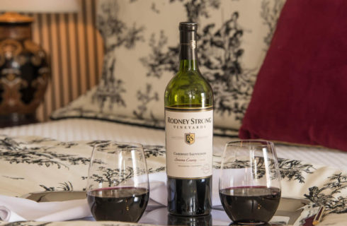 A wine bottle and two stemless glasses on a tray lying on a bed.