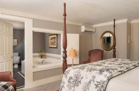 A large four post bed faces a bathroom with a soaking tub and grey tiled floor.