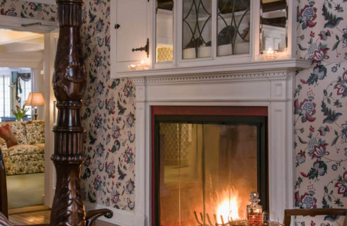 Glass enclosed fireplace in a bedroom with chintz wallpaper and an ornate four-post bed.