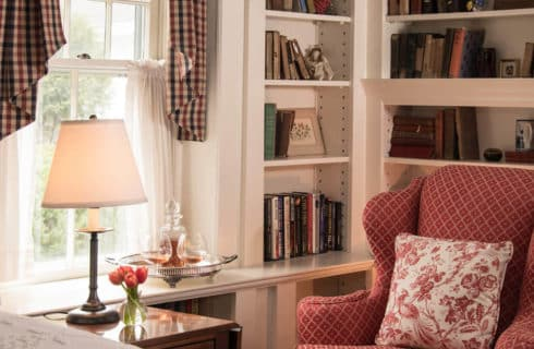 Corner of a bright bedroom with built in library shelves, a red wingback chair and a large window next to the bed.