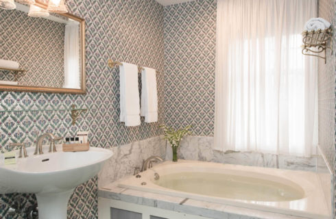 Bathroom with pedestal sink, soaking tub and blue patterned wallpaper.