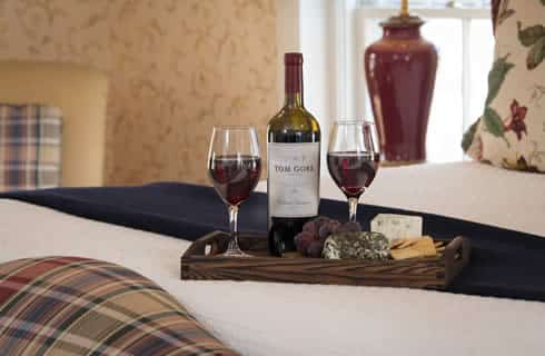 Wine bottle and two glasses with cheese and grapes laying on a bed with white covers.