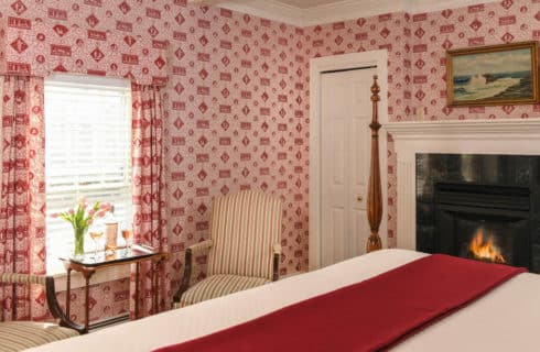 Bedroom with unique red wallpaper and matching drapes, two fabric chairs, a four-post bed and fireplace.