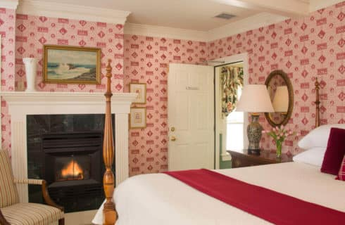 Bedroom papered in red pattern with a four-post wooden bed, a fireplace and a chair.