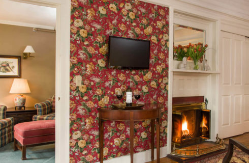 Guestroom with red chintz wallpaper, a tv, a fireplace and a sitting area with plaid armchairs.