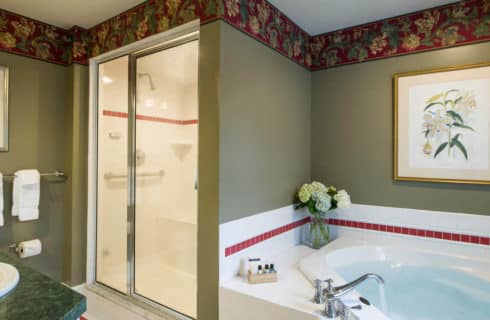 Big bathroom with a large soaking tub, a shower enclosure and a vanity with a green countertop.