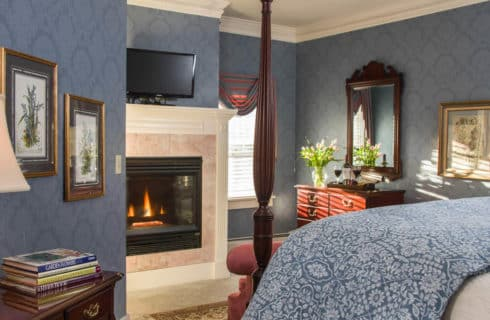 Bedroom with blue wallpaper, a four-post bed and fireplace with a TV above it.
