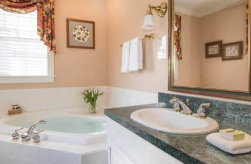 Bright and clean bathroom with a large soaking tub and a cabinet sink in white with a green counter.