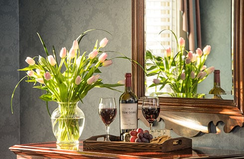 A dresser or side table with vase and pink tulip bulbs, next to a tray of red wine, with a mirror in the background, tulips visible in mirror.