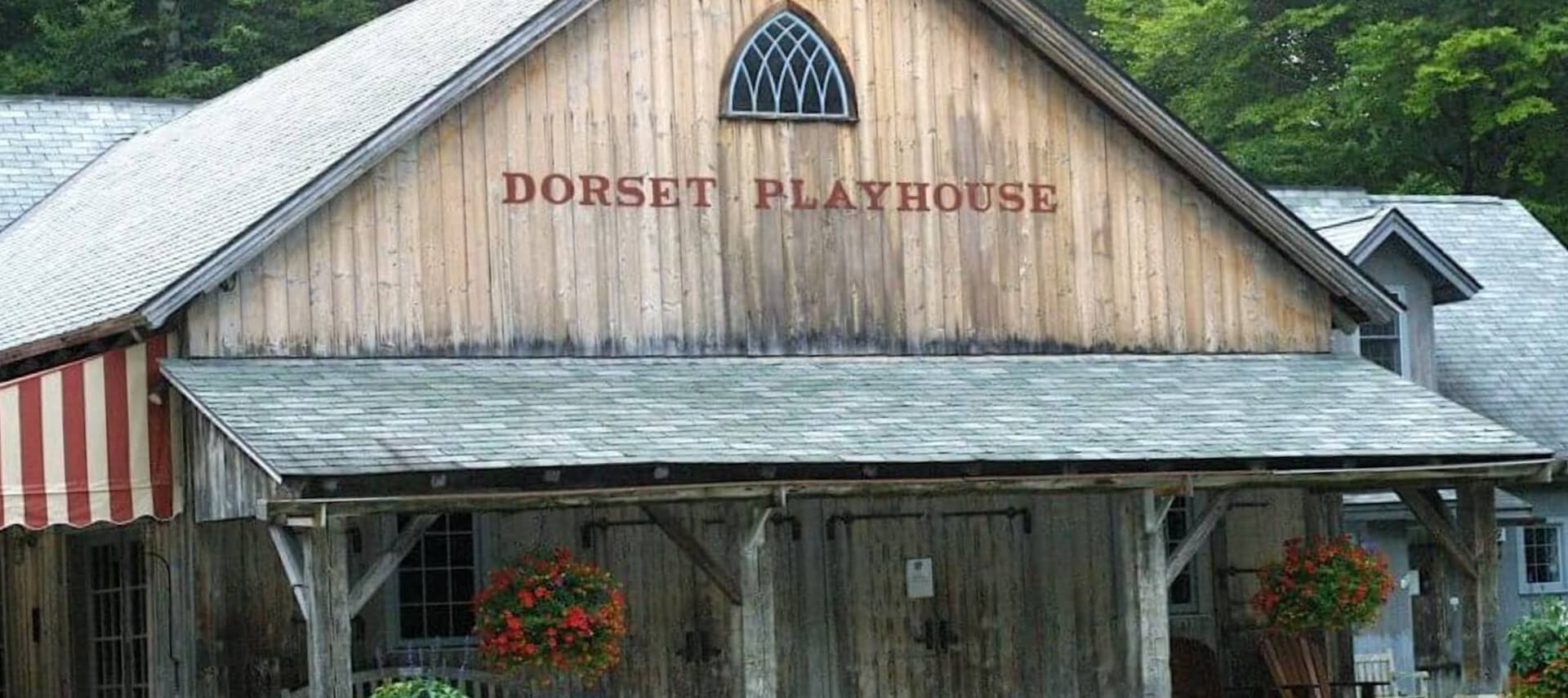 Large wooden building with red striped awnings and a sign that says Dorset Playhouse.