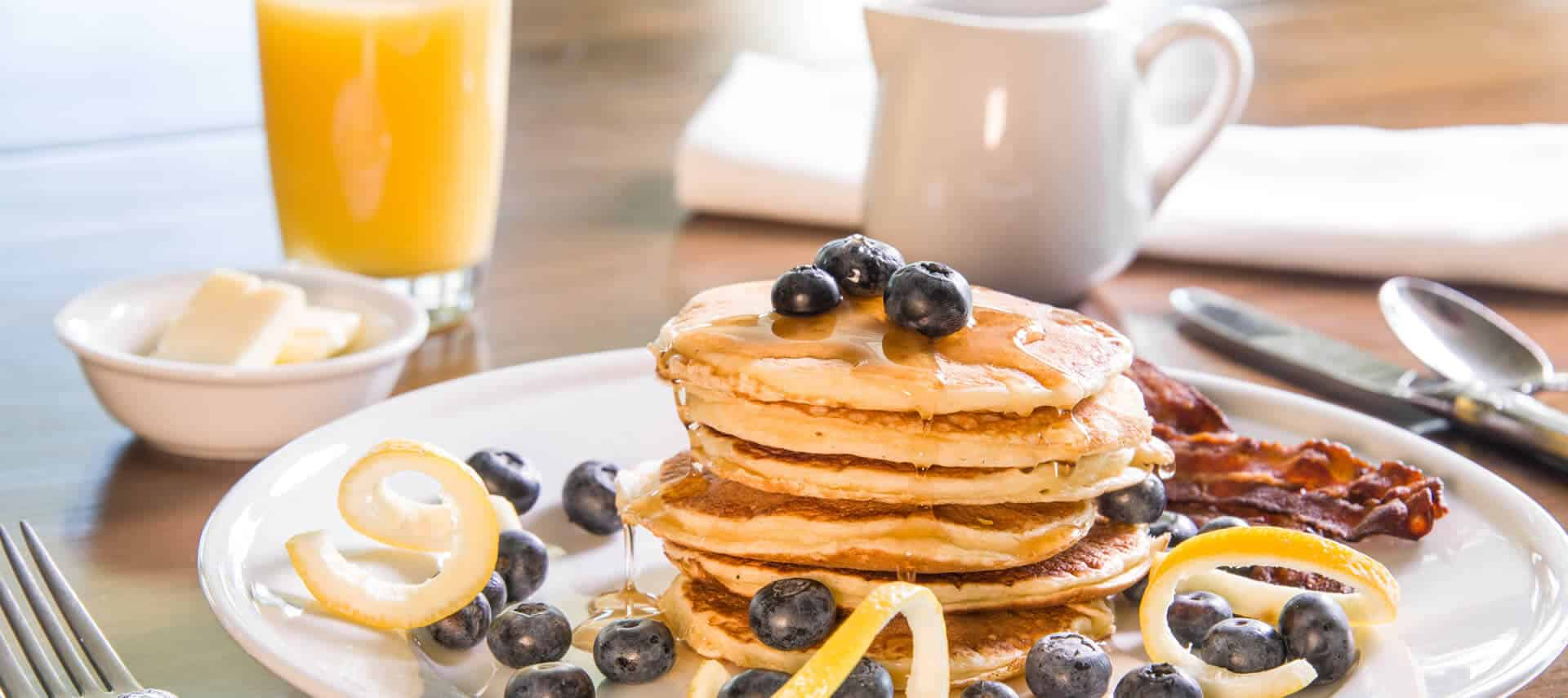 A stack of fluffy pancakes garnished with blueberries accompanies bacon on a white plate next to syrup and juice.