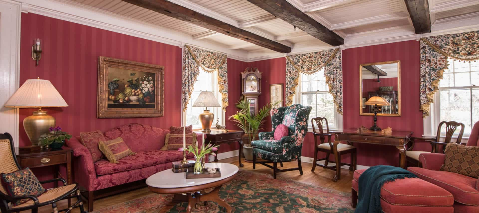 Attractive sitting room papered in red with a sofa, comfortable chairs and a small table desk.