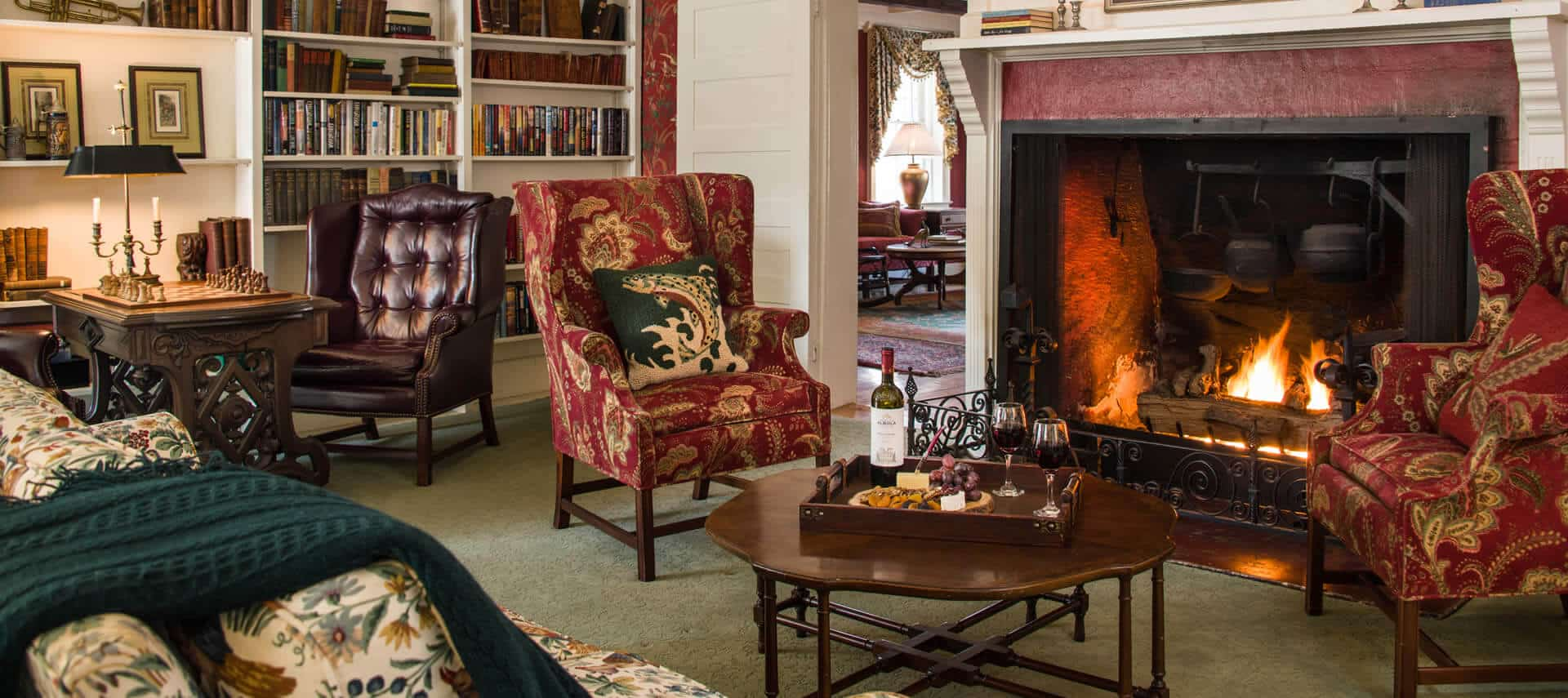 Cozy room with a fireplace, sofa, wingback chairs and a table for games.
