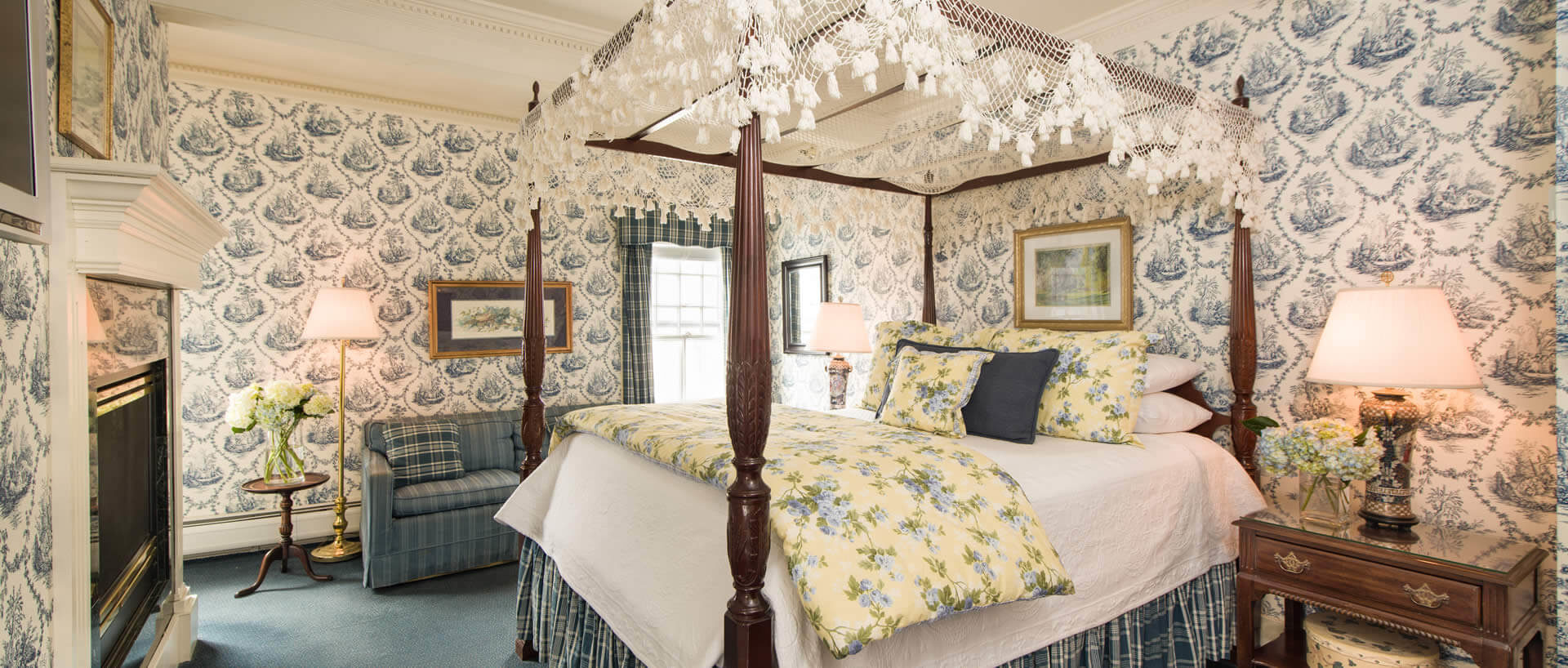 Elegant room with a large canopy bed, blue patterned wallpaper, blue carpets and a fireplace.