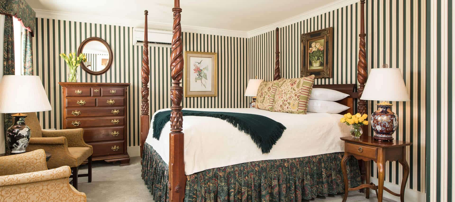 Charming room with a four-post bed, two chairs, green striped wallpaper, and elegant antique wooden furniture.
