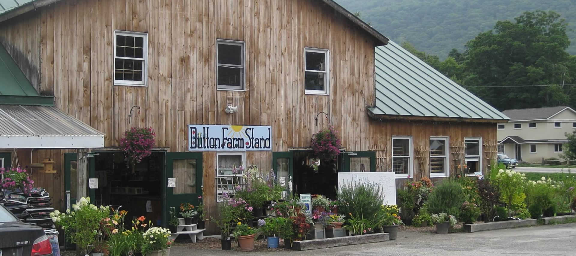 Wooden barn building surrounded with plants and flowers with a sign that says Dutton Farm Stand.