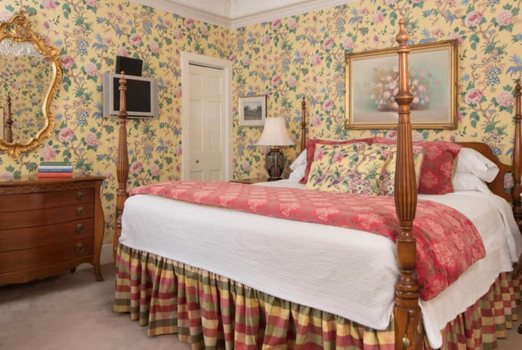 Bedroom with yellow chintz wallpaper, a four-post bed, antique wooden furniture and a red wing back chair.