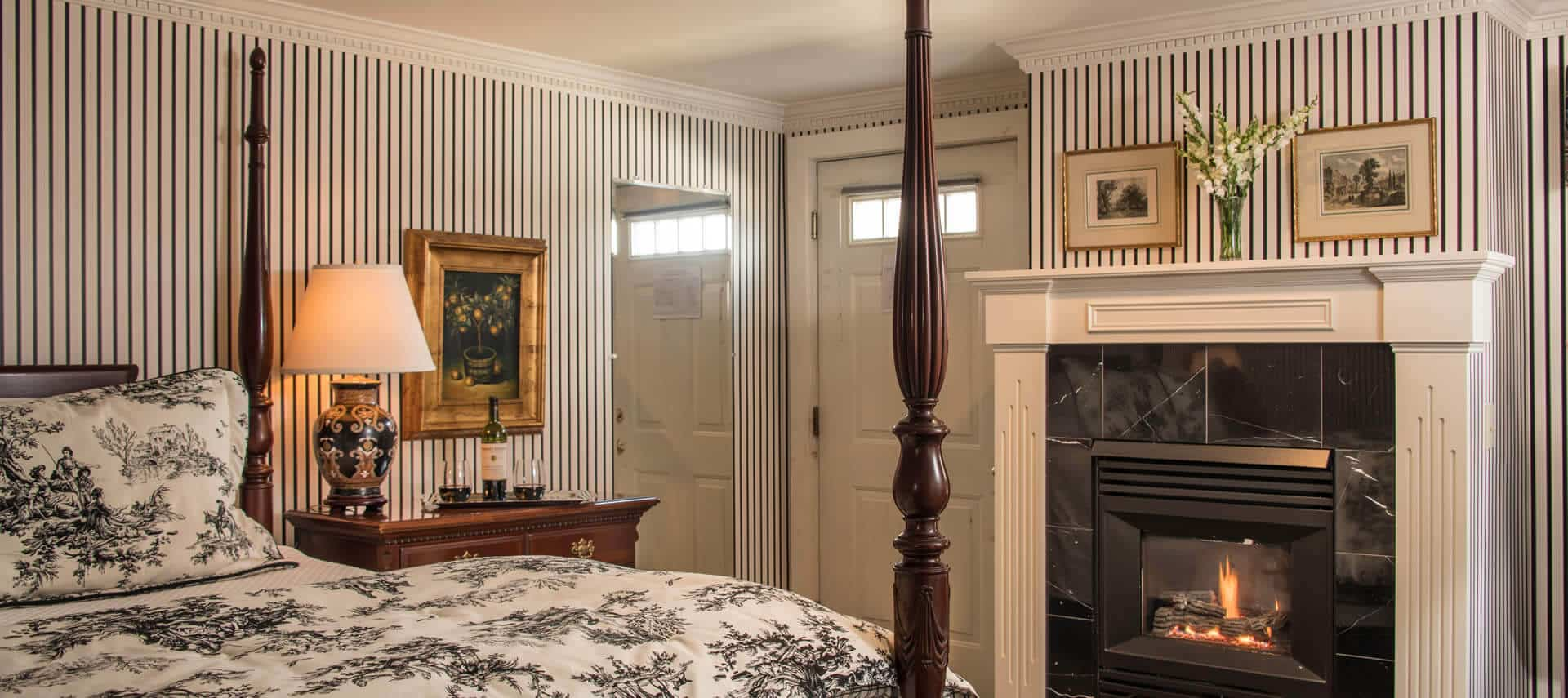 Bedroom with striped wallpaper, a fireplace and a four-post bed with a black and white patterned cover.