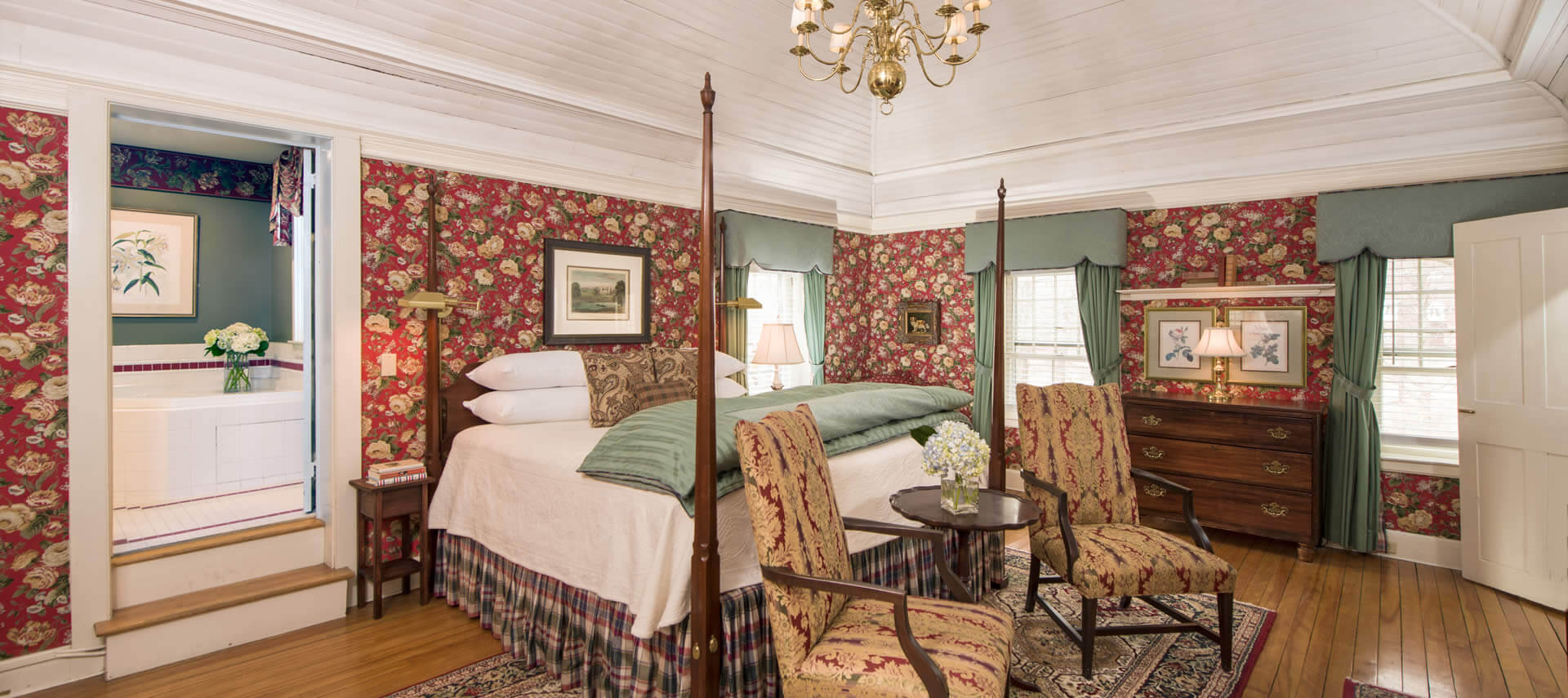 Guestroom with red chintz wallpaper, a four-poster bed, two chairs and windows with green drapes.