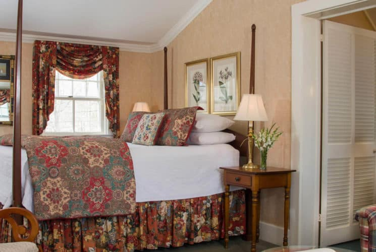 Sweet guestroom holding a large four-post bed, with chintz covers, a chair and sofa and two smaller windows.