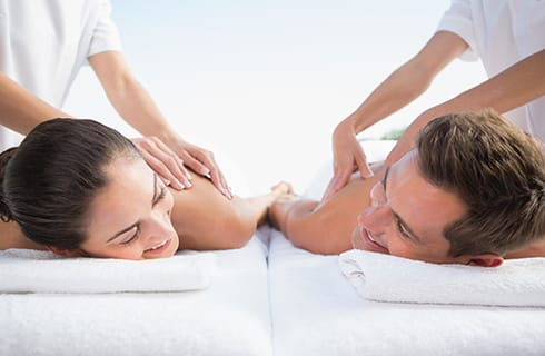 A male and female couple lying on white linens being massaged next to each other by massage therapists in white outfits under a pale blue sky.